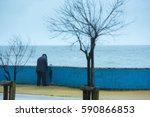 Small photo of An elderly man suffering from prostate adenoma - prostatit, relieve themselves while walking in the rain on the waterfront. The concept of the medical theme. Illustration diseasesymptoms.