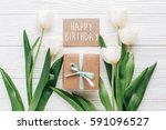 Small photo of happy birthday text sign on greeting card with stylish present box and tulips on white wooden rustic background. flat lay mock up with flowers and empty paper with space for text