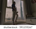 Small photo of Self portrait model man looking out at Burj Khalifa tower from the hotel room, Rove hotel Downtown Dubai February 2017