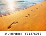 beach  wave and footprints at... | Shutterstock . vector #591576053