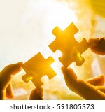 Small photo of two hands trying to connect couple puzzle piece with sunset background. Jigsaw alone wooden puzzle against sun rays. one part of whole. symbol of association and connection. business strategy.