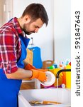 man makes cleaning the kitchen. ... | Shutterstock . vector #591847643