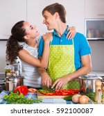 Small photo of Happy young husband helping smiling wife to prepare healthy dinner