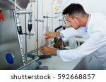 man in white coat working on... | Shutterstock . vector #592668857