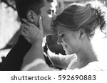 bride and groom posing on the... | Shutterstock . vector #592690883