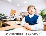 a small boy sits at the desk | Shutterstock . vector #59273974
