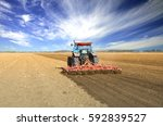 Small photo of Agriculture. Farmer in tractor preparing land for the next season. Cultivated field with beautiful countryside arable farmlands. Agronomy concept.