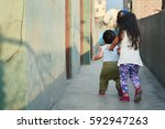 poor latin siblings playing  | Shutterstock . vector #592947263