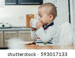 a child drinks a cup of tea ... | Shutterstock . vector #593017133