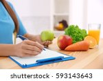 female nutritionist counting... | Shutterstock . vector #593143643