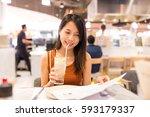 woman picking dish in menu at... | Shutterstock . vector #593179337
