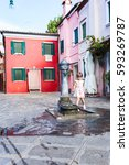 Small photo of The girl washes hands in fountain. The first acquaintance with fountains of island of Burano