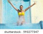 woman sliding down on water... | Shutterstock . vector #593277347