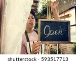 woman hanging open sign by the... | Shutterstock . vector #593517713
