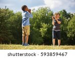 two boys playing tin can... | Shutterstock . vector #593859467