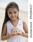 Small photo of Young girl on beach holding giant conk shell in her hands, smiling