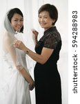 a bride and her mother smile at ... | Shutterstock . vector #594288983