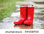 Red gumboots in rain full of water - stock photo