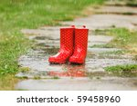 Red gumboots in garden grass - stock photo
