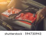 Small photo of A car mechanic replaces a battery / soft focus picture