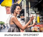 pretty woman buying a hot dog... | Shutterstock . vector #595293857