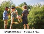 girl jumps thourgh hula hoop...   Shutterstock . vector #595615763