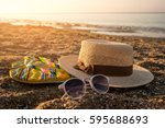 hat with sunglasses on sand.... | Shutterstock . vector #595688693