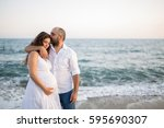 happy young pregnant couple... | Shutterstock . vector #595690307