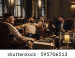 Small photo of Three men are enjoying drinks in a bar lounge. They are talking and laughing while drinking pints of beer.