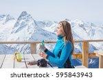 a woman snowboarder drinking... | Shutterstock . vector #595843943