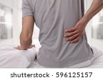 man suffering from back pain at ... | Shutterstock . vector #596125157