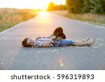 Small photo of A shepherd puppy gets acquainted with her little master who lies on the asphalt against the sunset