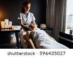 massage therapist massaging... | Shutterstock . vector #596435027