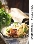 Small photo of Nicely served spaghetti carbonara on black background with arty garnish
