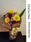 Small photo of the holiday gift bouquet of flowers of yellow gerberas, Alstroemeria Alstroemeria and green leaves in a brown gift paper