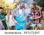 happy friends grilling meat and ... | Shutterstock . vector #597172247