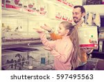 Stock photo portrait happy father and daughter choosing pretty bird for keeping in pet shop 597495563