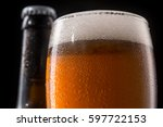 Small photo of Glass of beer in macro. Tiny water drops add together and flow down the cold beer glass with froth. Unopened brown bottle neck in blurred black background.