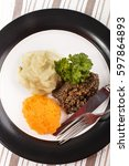 Small photo of typical scottish dish, haggis with mashed potato, turnip and parsley on a plate