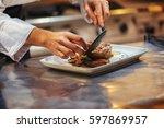 chef in restaurant arrangin and ...   Shutterstock . vector #597869957