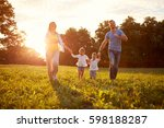 beautiful young family running... | Shutterstock . vector #598188287
