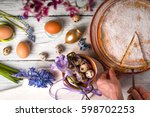 Small photo of German Easter cake, a piece of cake, eggs, flowers, ribbons on a table