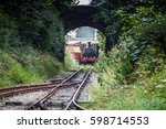 Small photo of Train tracks. Train is arriving to the station. Arriving train goes by rail track. Steam train arriving. Arrival of the trains. Steel tracks crossing. Powerful locomotive arrive under the bridge city