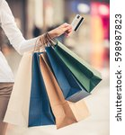 Small photo of Cropped image of beautiful girl with shopping bags and credit card doing shopping in the mall