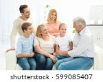 happy family sitting on sofa in ... | Shutterstock . vector #599085407