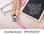 Small photo of Pink stethoscope and a thermometer with a notice board with word ACHILLES TENDON INJURY on top of wooden table. Medical and education concept.
