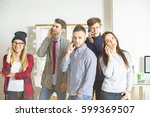 Small photo of Group of beautiful young people in office talking on their phones all at once. Communication concept