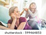 daughter braiding mother's long ... | Shutterstock . vector #599464853