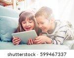 happy siblings lying on sofa at ...   Shutterstock . vector #599467337