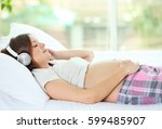 pregnant woman listening to... | Shutterstock . vector #599485907